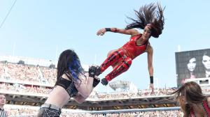 Brie Bella with a flying dropkick