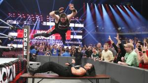 Kevin Owens frog splashes Roman Reigns