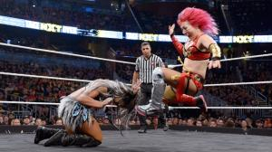 Asuka delivers a running kick to Ember Moon