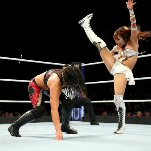Kairis Sane hits an axe-kick on Shayna Baszler